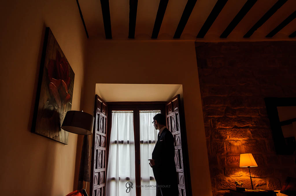 fotos del novio junto a ventana en boda civil en Ubeda