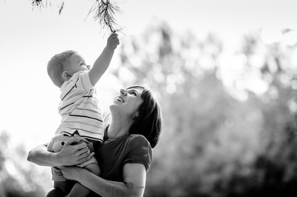 reportaje de fotos divertidas en familia bebé agarra rama de árbol