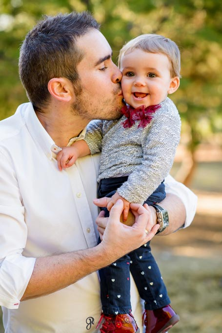 reportaje de fotos divertidas en familia el padre besa a su bebé