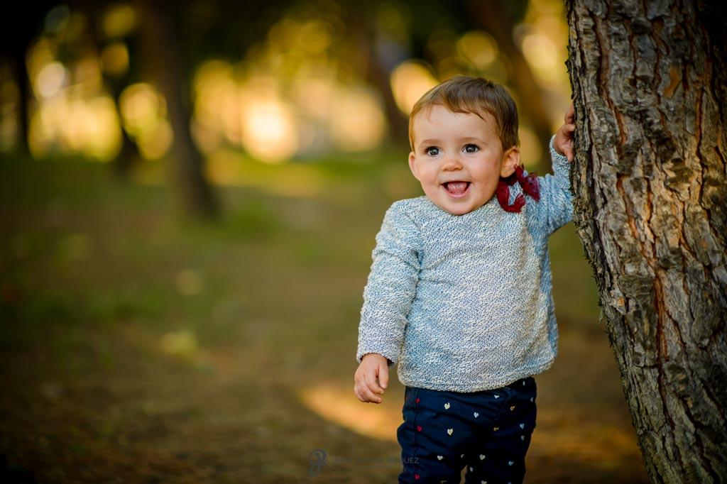 reportaje de fotos divertidas en familia bebé se apoya en árbol
