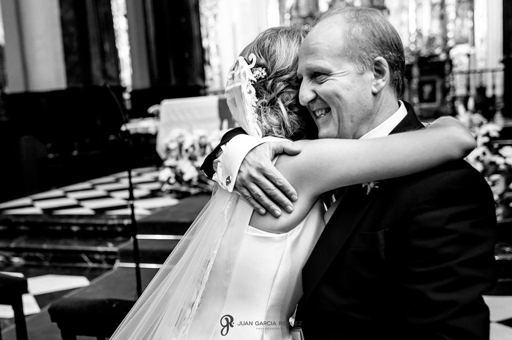 Un padre emocionado dándole un abrazo a su hija