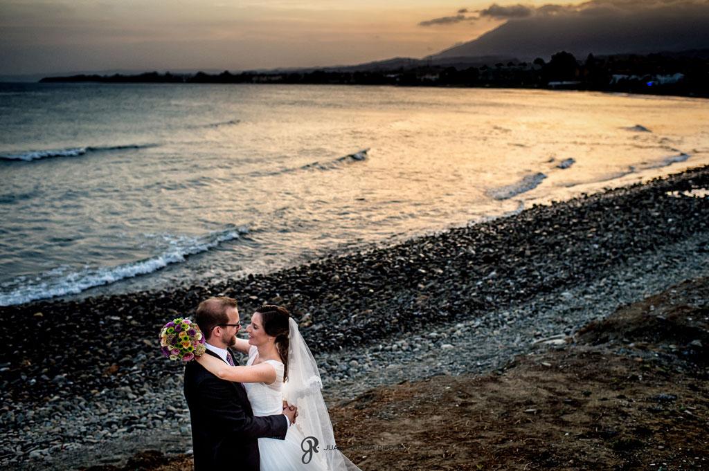 fotografía de unos novios en una boda en la playa al atardecer