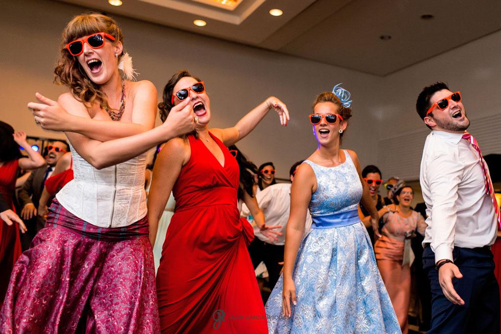 foto divertida de amigos bailando flashmob en una boda en la playa