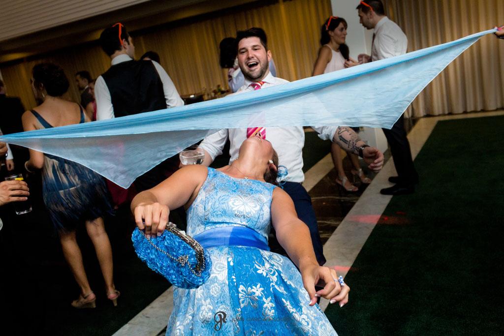 fotografía divertida de amigos bailando en la fiesta de una boda en la playa