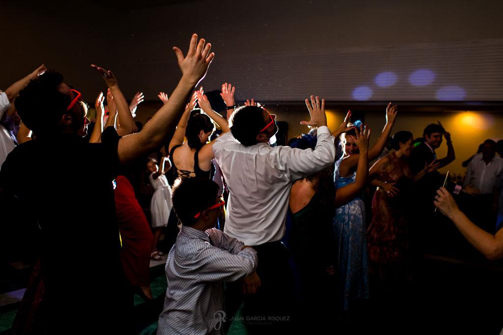 foto impactante de amigos de los novios bailando en su boda en la playa