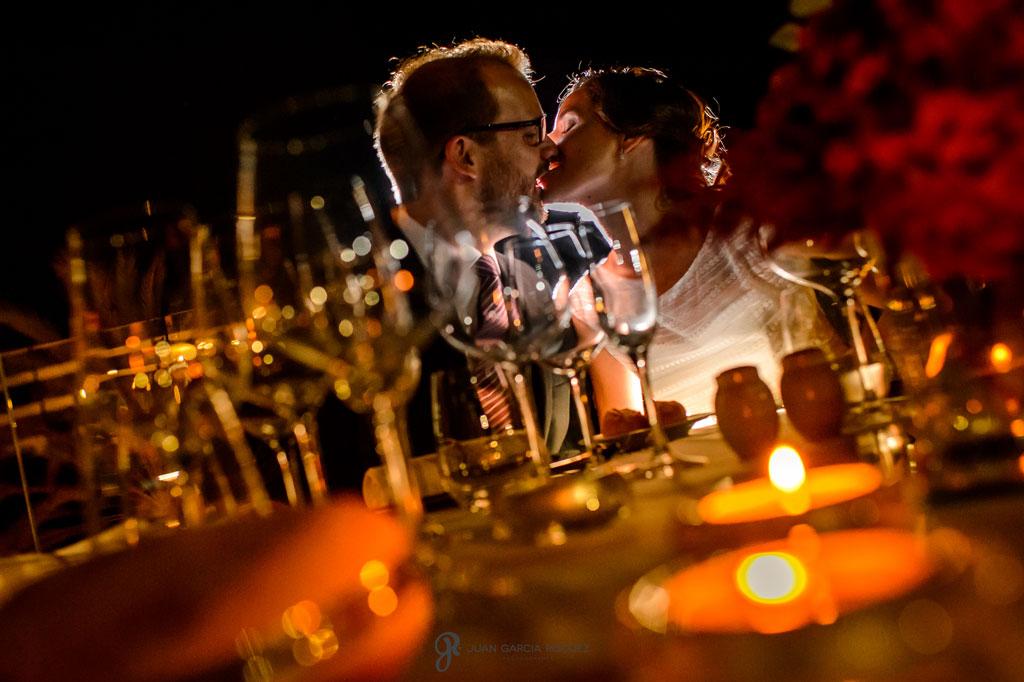 fotografia romántica de unos novios besándose bajo la luna en su boda