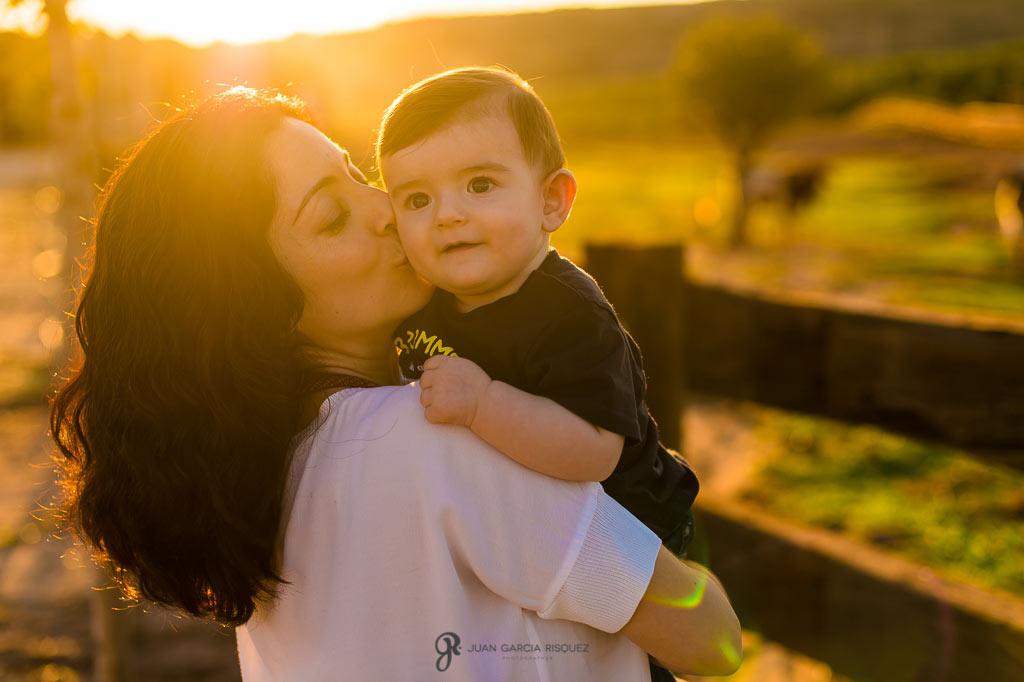 Madre besando a su hijo al atardecer