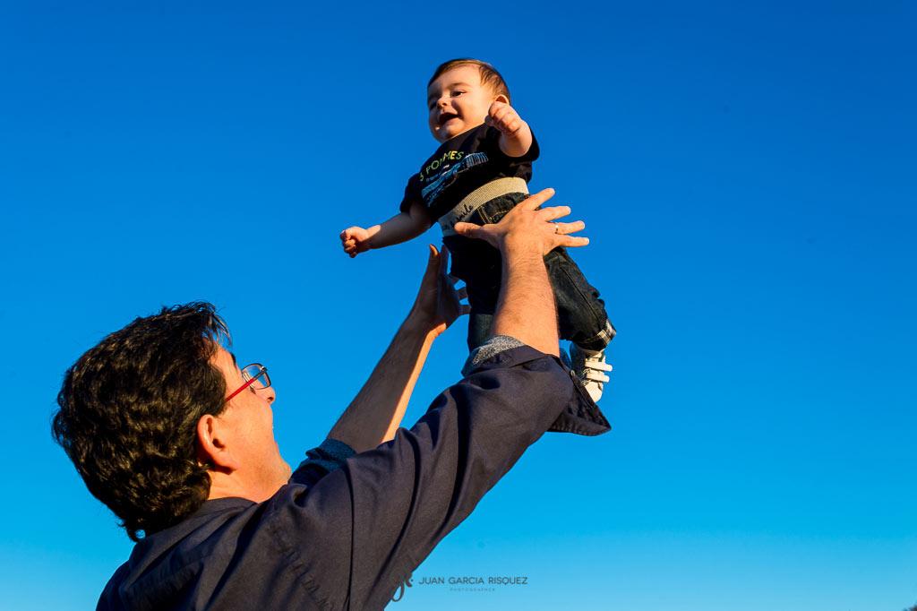 Imagen de un padre lanzando a su hijo al aire