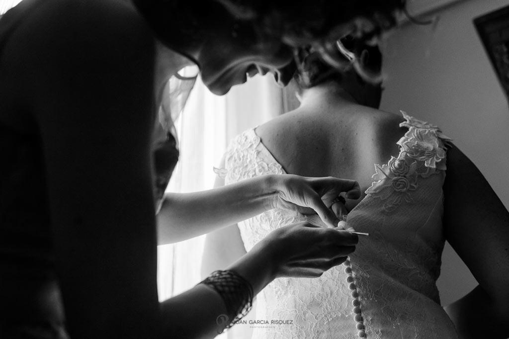 Detalle de la novia mientras se pone su vestido