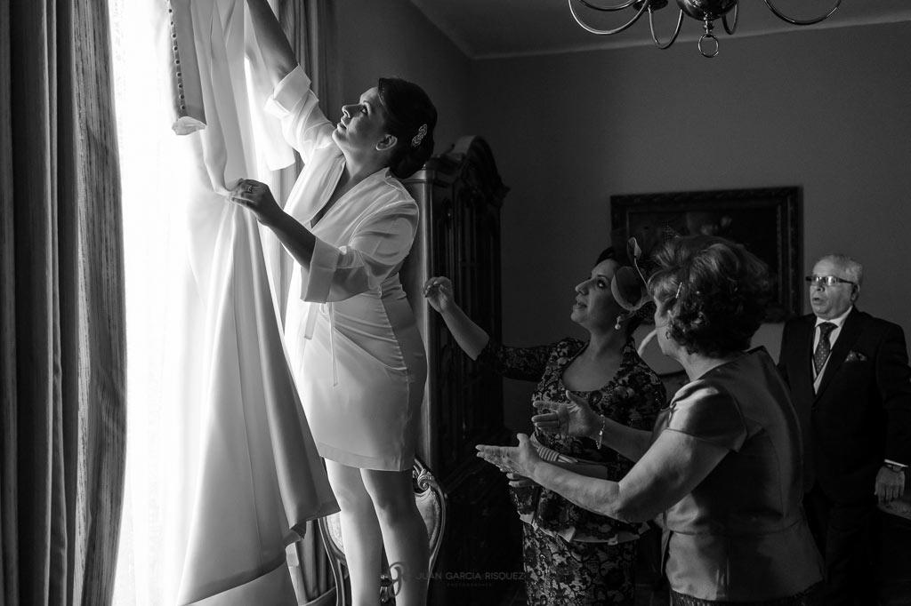 La novia cogiendo su vestido antes de ponerselo