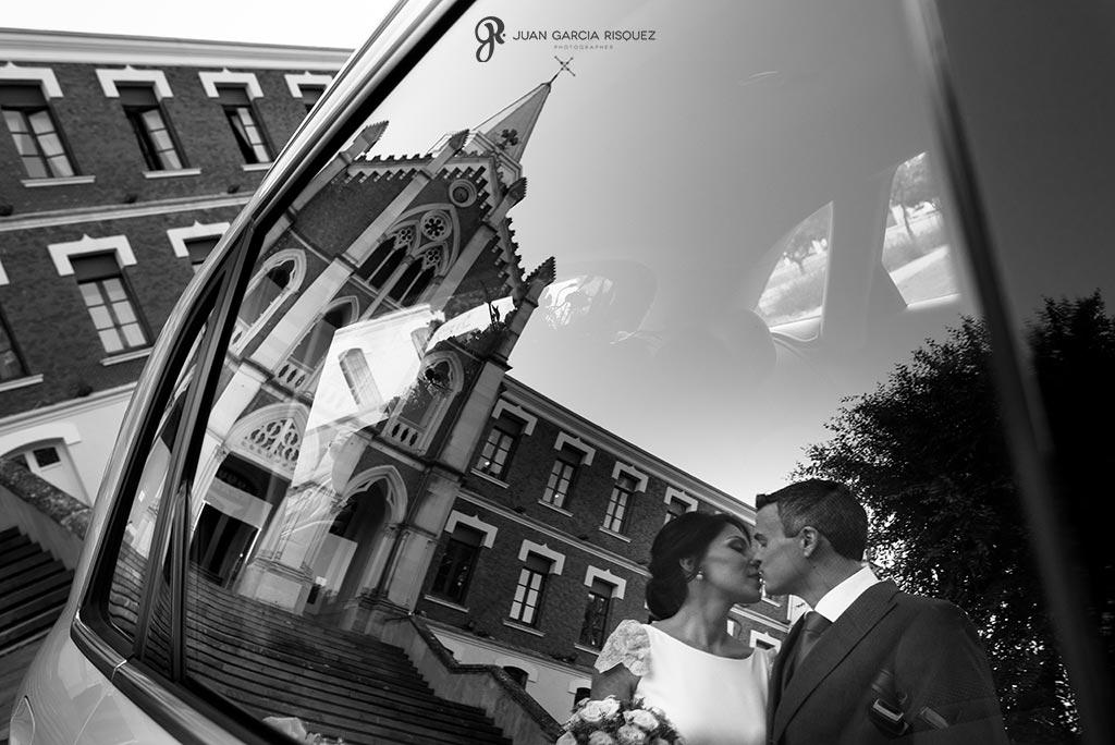 Reflejo de novios besándose a la salida de la iglesia