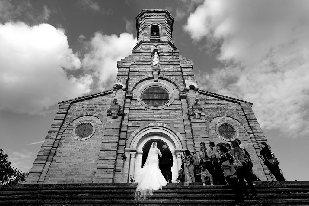 Novia caminando del brazo de su padre hacia la ceremonia religiosa