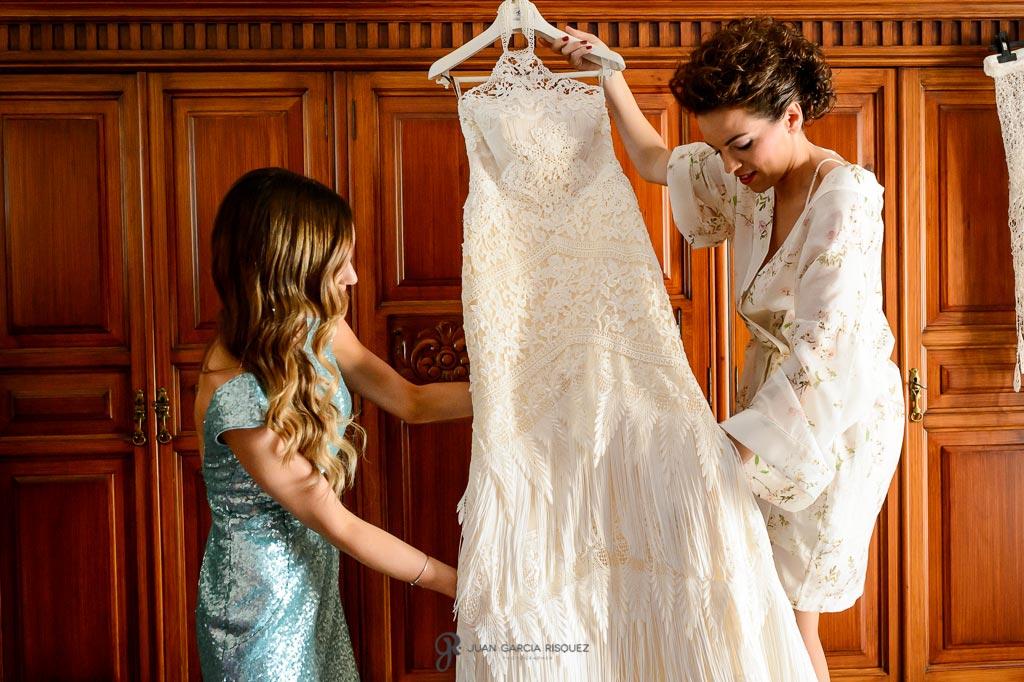 Hermana ayuda a la novia a coger el vestido