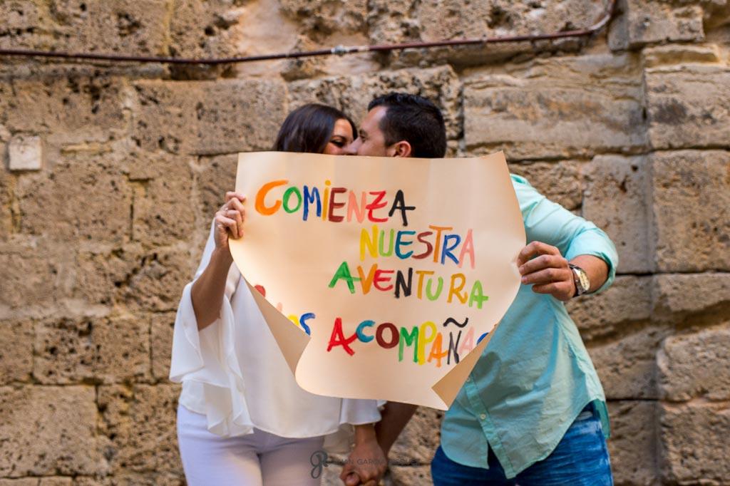 Pareja con un cartel anunciando su compromiso por las calles de Granada