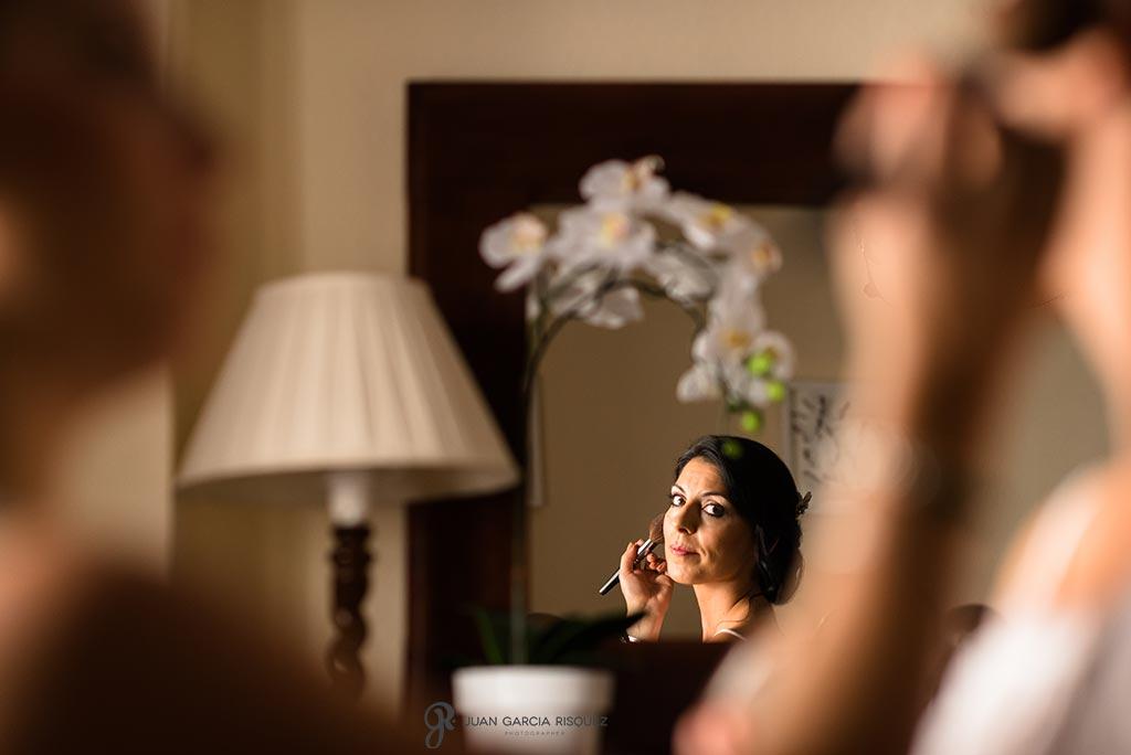 Novia se mira en el espejo mientras le maquillan