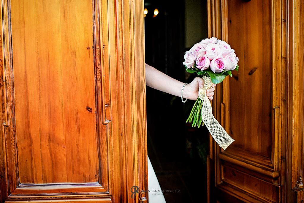 Novia sale por la puerta de su casa con su ramo
