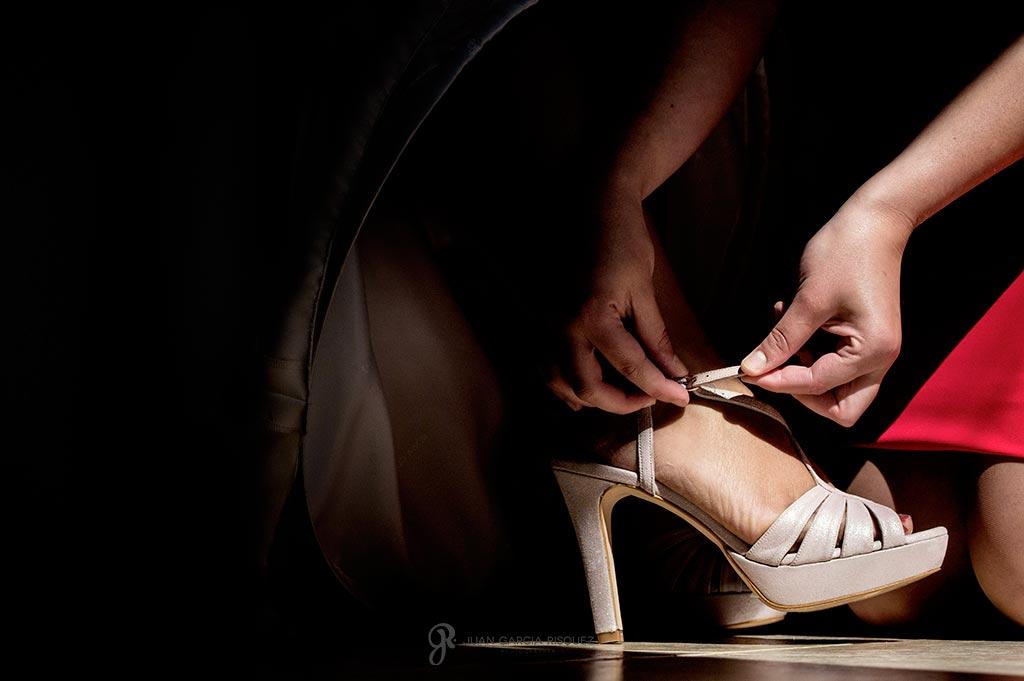 Amiga ayuda a la novia a ponerse el zapato