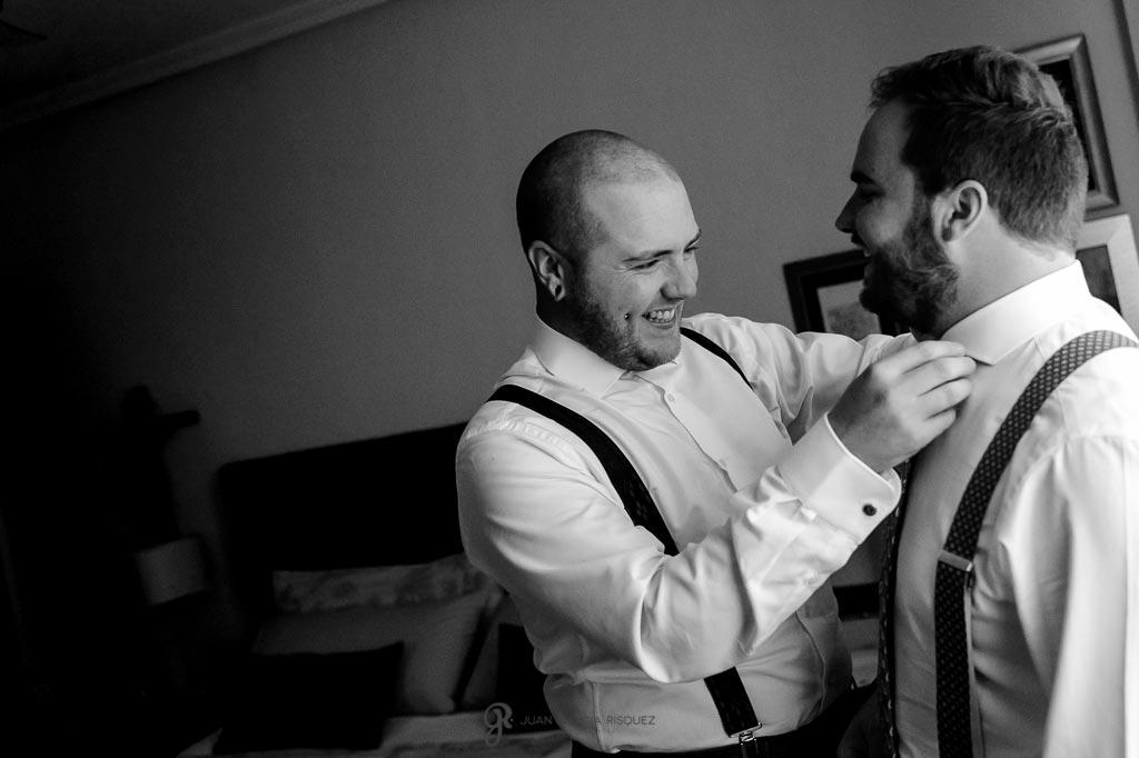 Hermano del novio ayudándolo a vestirse para su boda