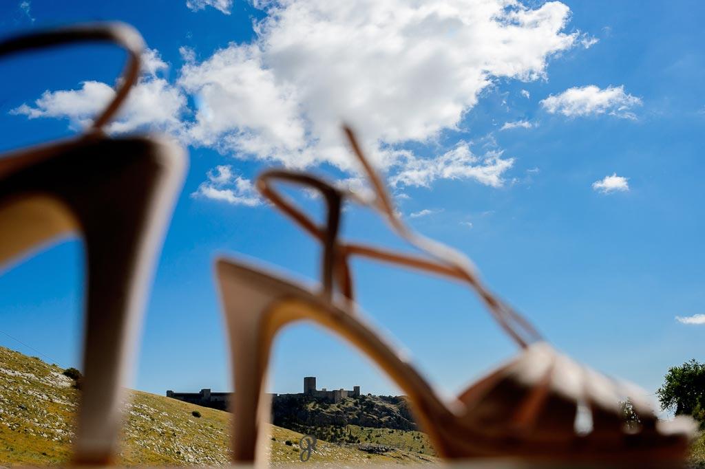 Fotografía de zapatos de novia con un castillo de fondo