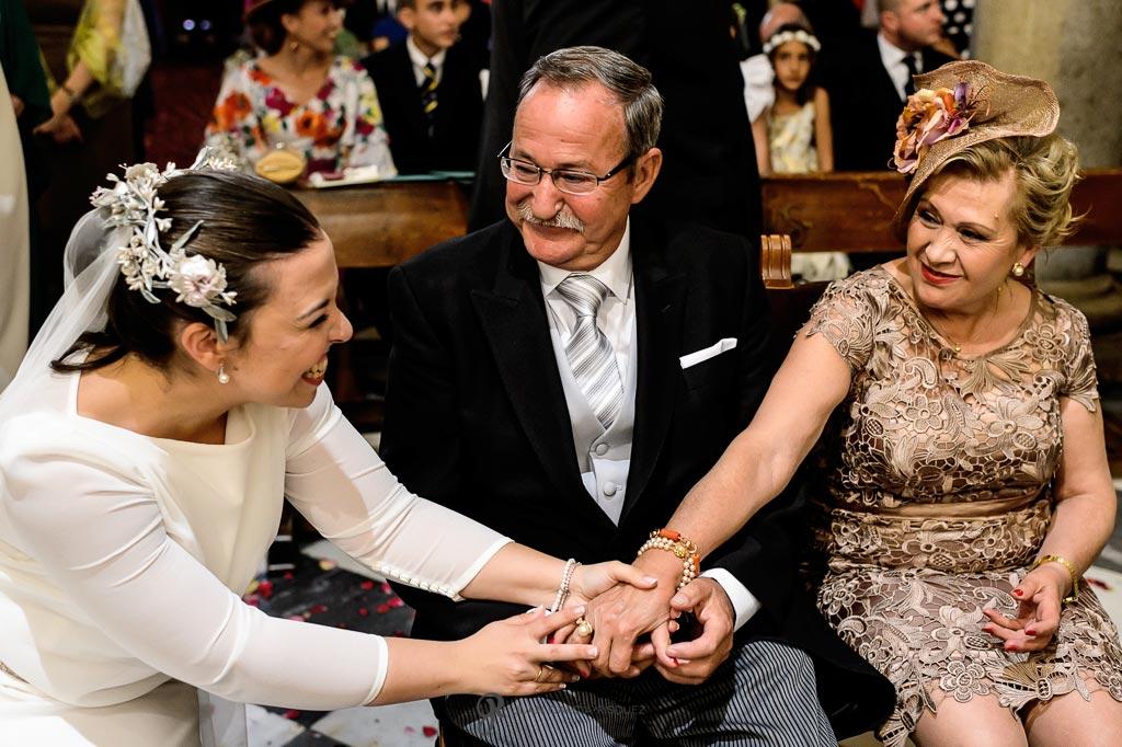 Fotografia emocionante de una novia abrazando a sus padres en su boda