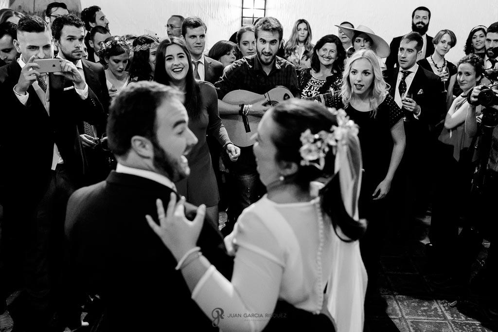 Fotografía de novios escuchando una comparsa de carnaval en su boda