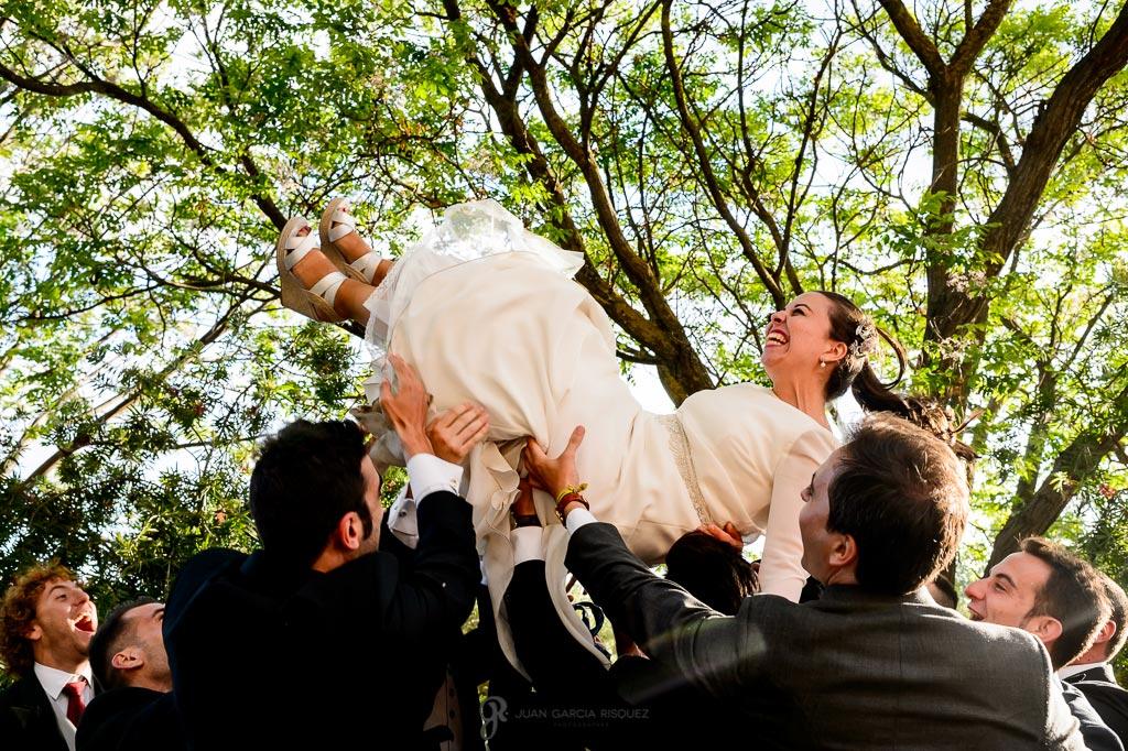 Foto de una novia manteada por los aires por los invitados