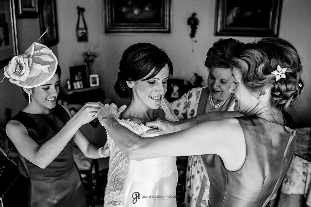 Familiares y amigas ayudan a vestirse a la novia