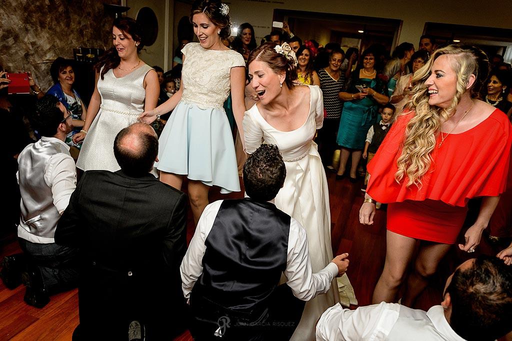 Novios bailan junto con sus amigos