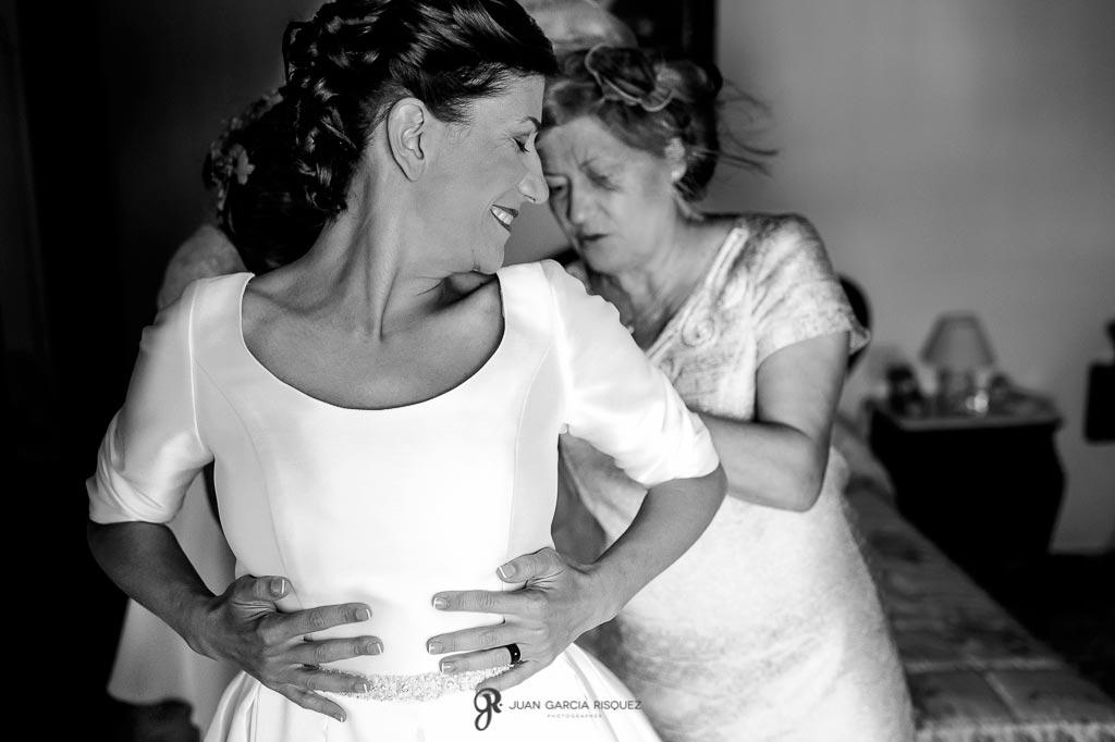La madre de la novia le ayuda a vestirse