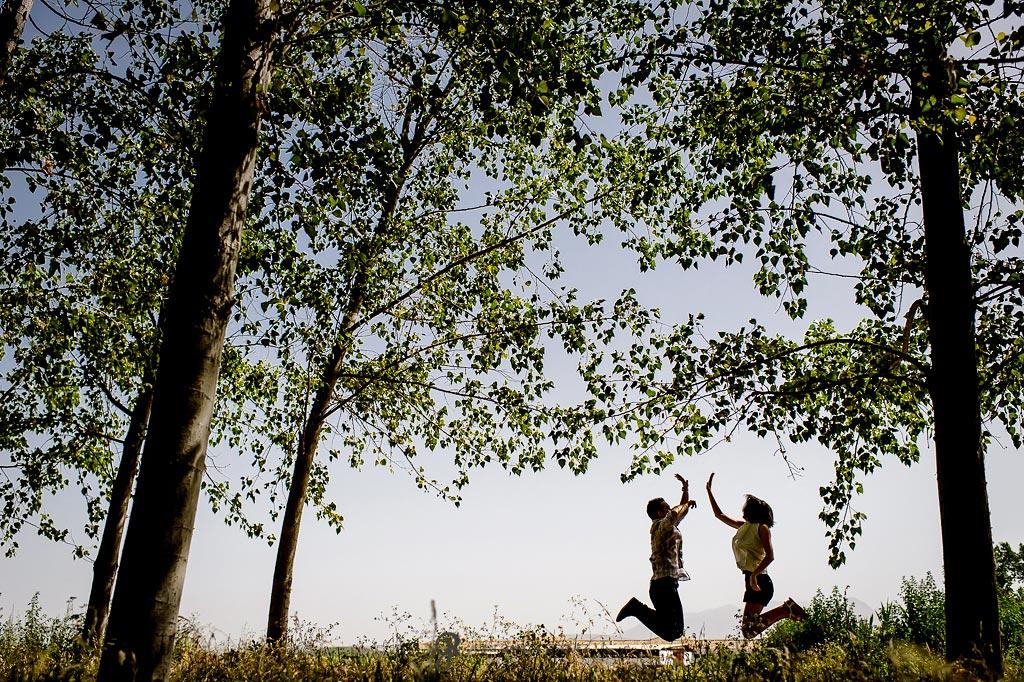 Novios saltando en el campo