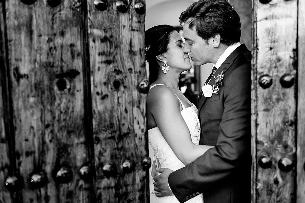 Novios se besan antes de entrar al salón de bodas