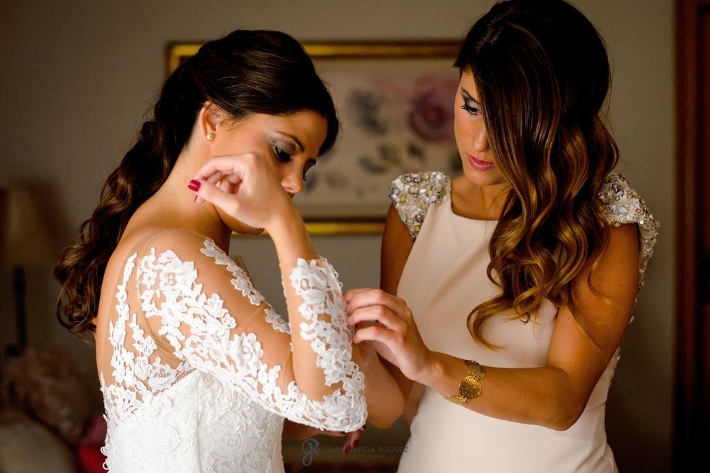 Hermana ayuda a la novia a vestirse