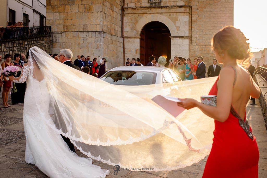 Amiga sostiene el velo de la novia antes de entrar a la iglesia