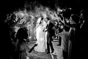 Novios sorprendidos entrando en su boda mientras sus amigos los reciben