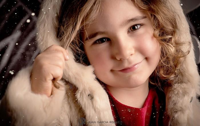 Niña posa sonriente en un decorado navideño
