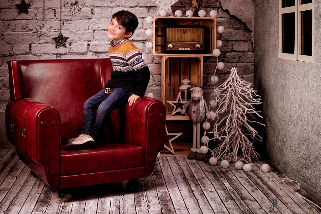 Niño posa en un decorado ambientado con atrezo típico navideño
