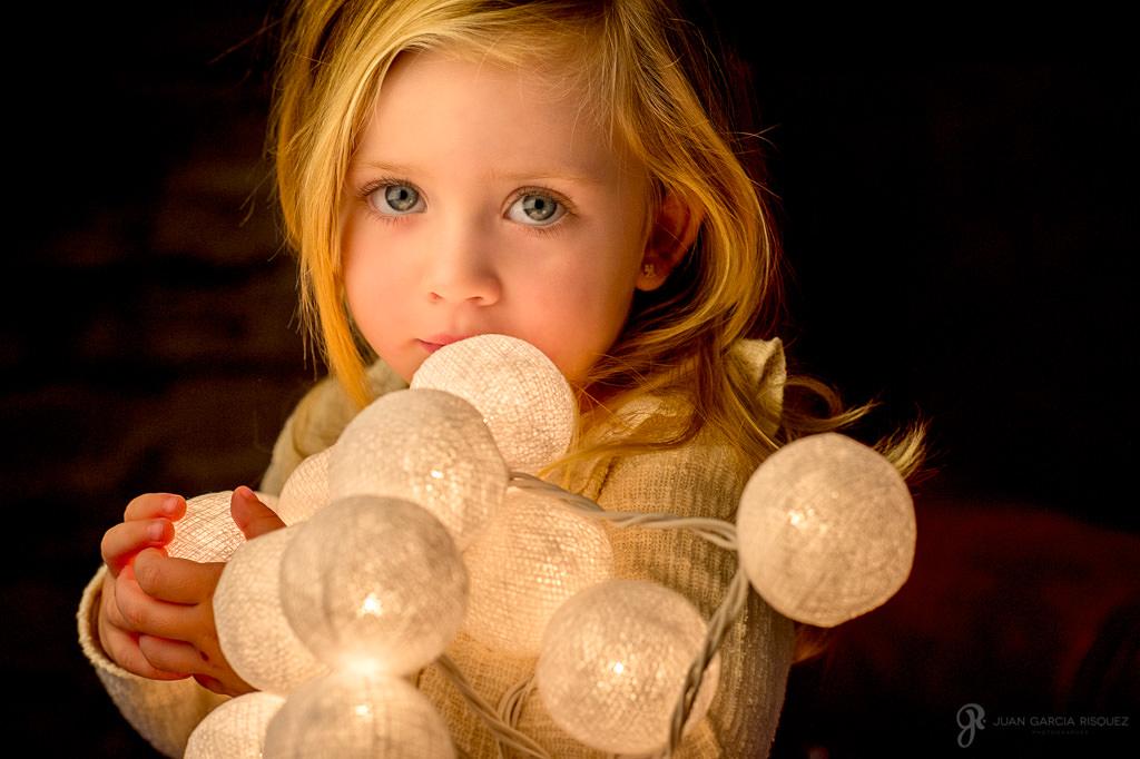 Niña posa sosteniendo luces típicas navideñas
