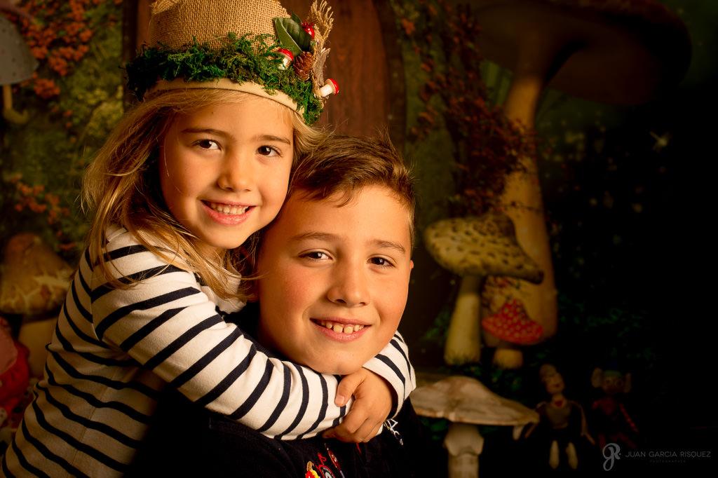 Hermanos abrazados posan en un decorado navideño