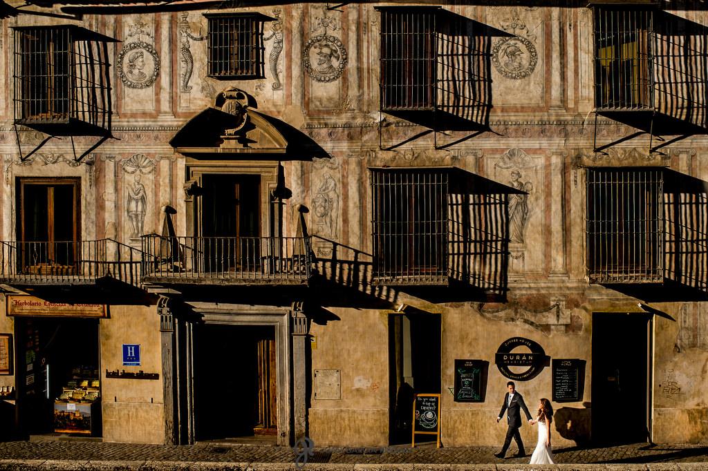 Novios felices paseando por el paseo de los tristes de Granada el día de su boda