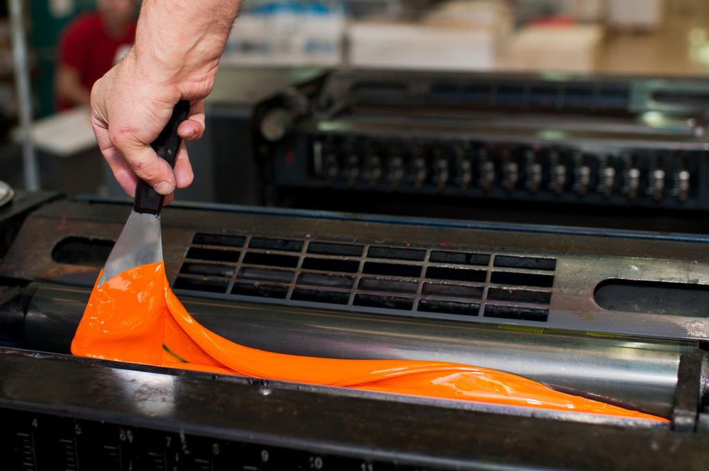 Fotos de un trabajador aplicando tinta a una máquina en Gráficas La Paz