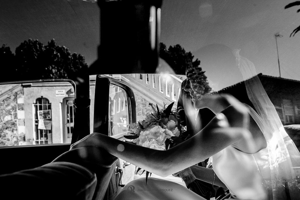 Foto de una novia bajándose de un coche clásico para ir a su boda en Granada
