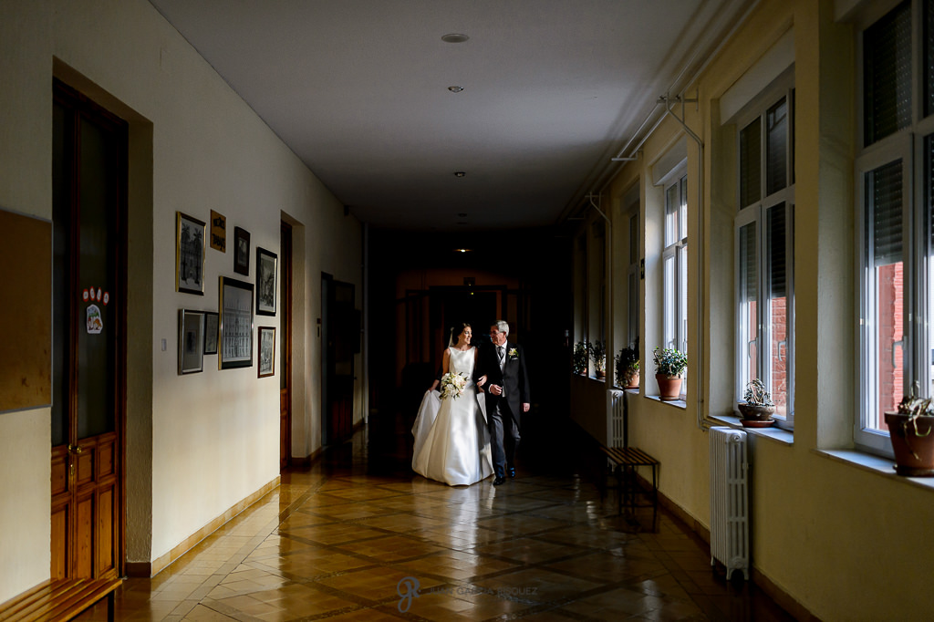 Novia entrando de la mano de su padre por el pasillo del colegio donde estudió