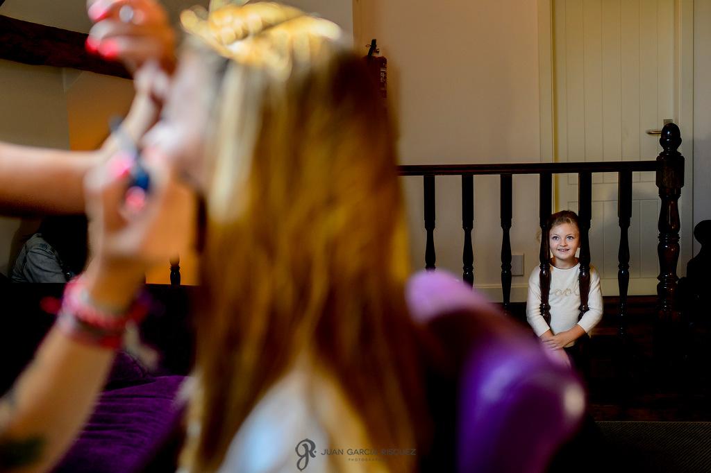 Foto creativa de una novia en su maquillaje con su sobrina antes de ponerse su vestido