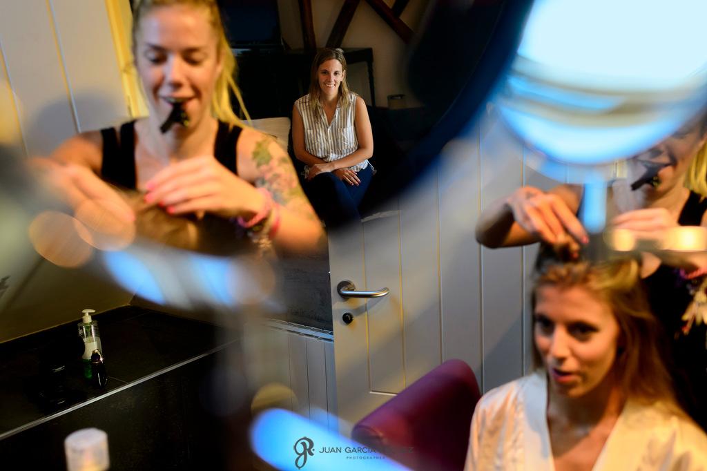 Foto creativa de una novia en su maquillaje con su hermana antes de ponerse su vestido