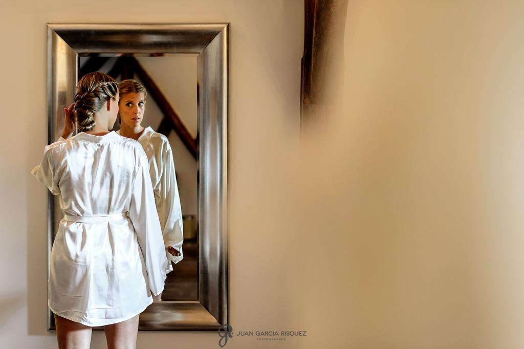 Fotos de una novia mirándose al espejo en bata momentos antes de la ceremonia