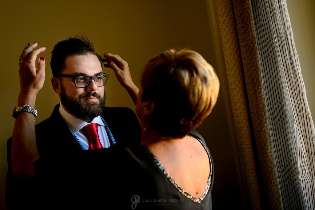 Fotografía de un novio mientras su madre le da el último toque antes de irse a su boda en Finca Fuentepizarro en Madrid