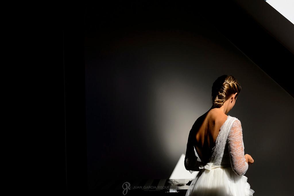 Foto de una novia con una luz de ventana y con un detalle de su vestido