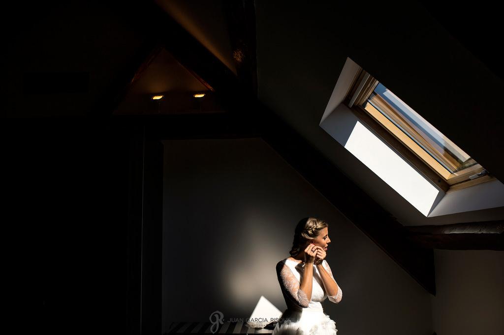 Reportaje fotográfico de una novia poniéndose los pendientes para irse a la ceremonia