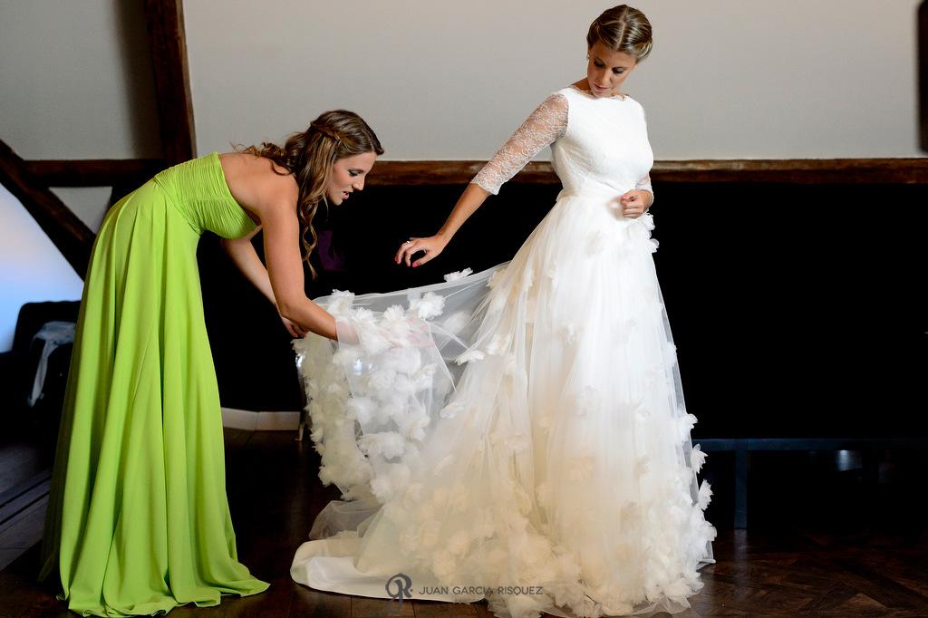 Fotografía de la novia y su hermana ayudándole a vestirse para su boda
