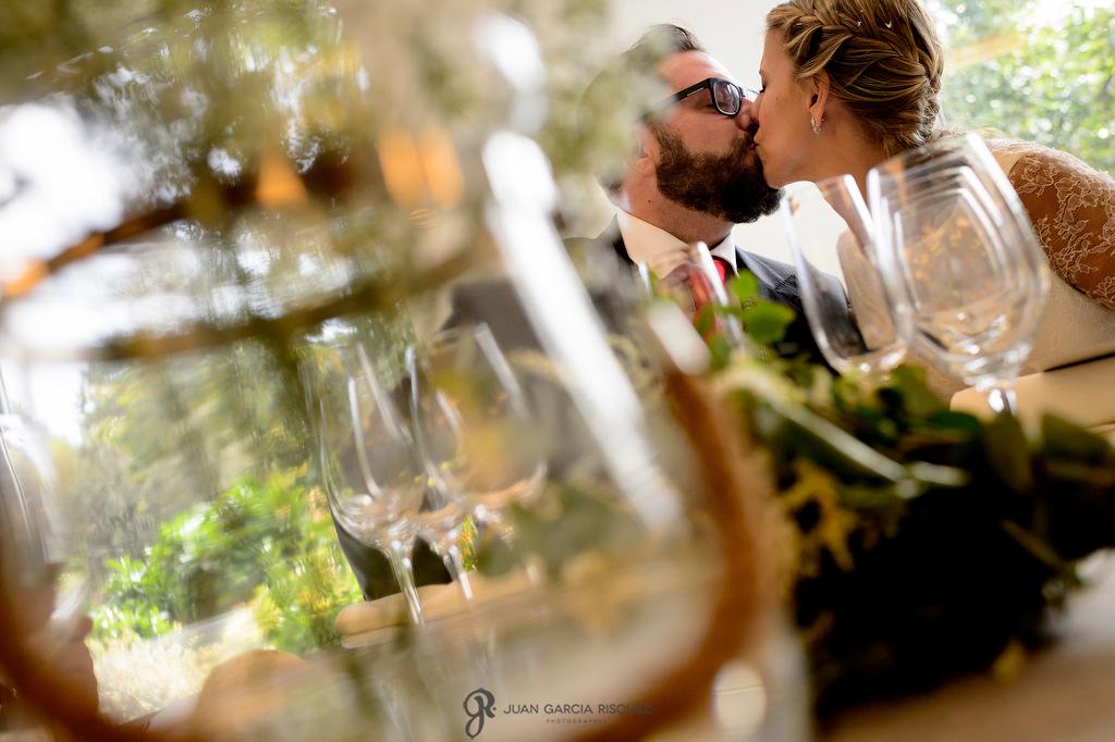 Fotografía de novios recién casados dándose un beso